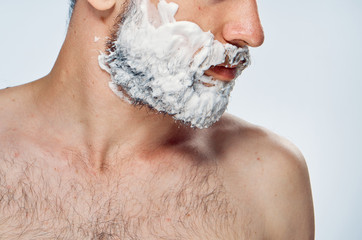 Young guy with beard on white isolated background in shaving foam
