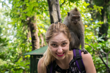 Woman interacting with a monkey in Bali, Indonesia