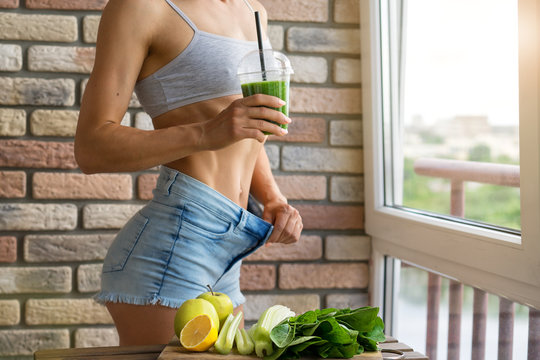 Fit woman drinking vegetable Green detox smoothie.  raw food diet
