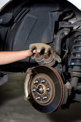 Girl inspects the calipers of a break from a pickup