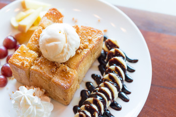 Honey toast with vanilla ice cream, whipped cream and chocolate syrup. Served with banana, grape and apple(selective focus)