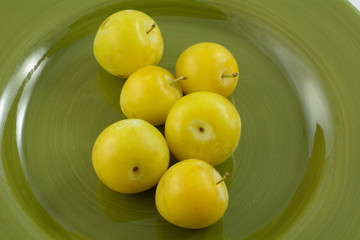 Close up of ripe yellow shiro plums on green plate