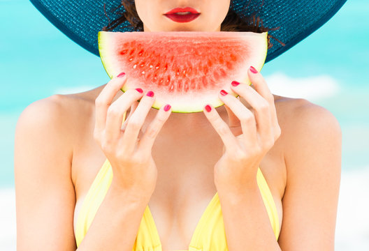 Summer colors. Girl holding slice of watermelon on the beach with red painted nails.
