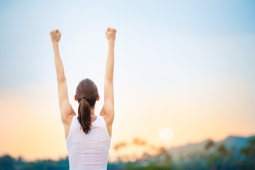 People winning achievement concept. Young woman with fist in the air celebrating success and happiness.