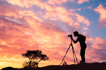 Nature photographer taking a picture outdoor. Photography and travel.