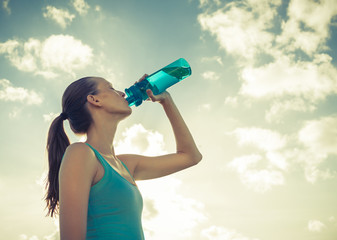 Woman drinking bottle of water outdoor on a hot summer day.
