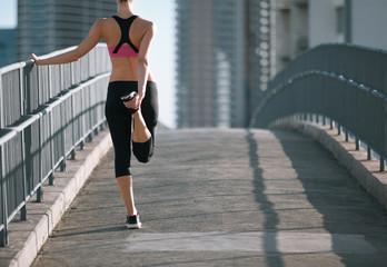 Female runner on city bridge warming up before run.