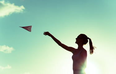 Girl throwing paper airplane in the air.