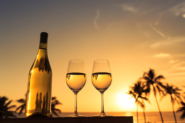 Pair of wine glasses and bottle of wine on the beach during sunset.
