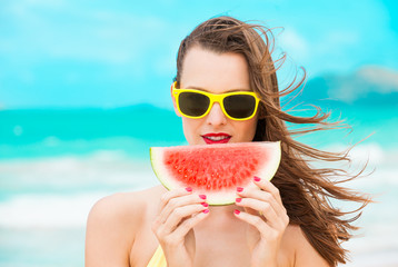 Portrait of beautiful girl on the beach holding slice of watermelon with red painted nails.