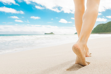 Beach holiday background. Closeup of woman walking down a white sand beach in Hawaii.