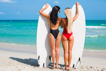 Two beautiful amazing tanned girls are surfing, blonde and brunette, stand on the seashore, waiting for the wave, sports ideal figures, sexy swimsuits, long hair, best friends photographed from behind