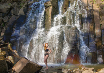 beautiful girl posing in a high waterfall, absolutely deserted redhead girl in a waterfall.