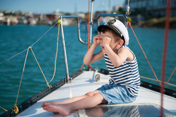 Funny little boy captain on a yacht in the summer