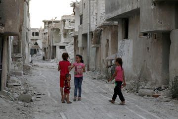 Syrian children are seen play amidst the rubble of damaged buildings in Deraa
