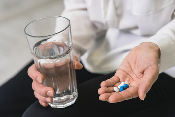 Senior woman with pills and a glass of water at home / People, medicine and health issues concept , closeup