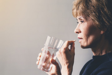 Adult woman with a pill and a glass of water / health care concept