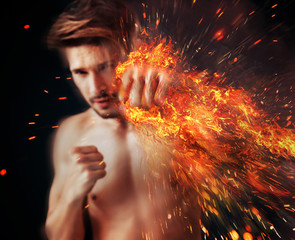 Handsome athlete punching with flame around his fist