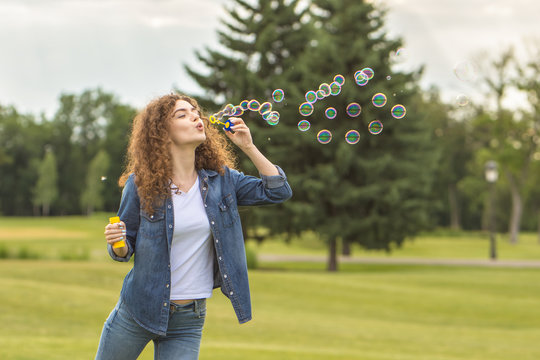 The happy woman blowing bubbles in the green park