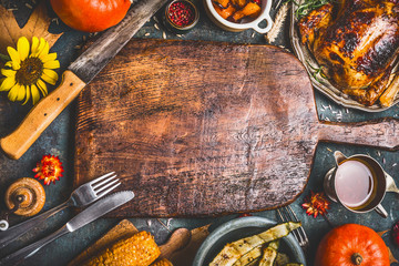 Thanksgiving dinner background with  turkey ,sauce,grilled vegetables,corn ,cutlery ,  pumpkin, fall leaves and flowers arrangements around wooden gutting board, top view.