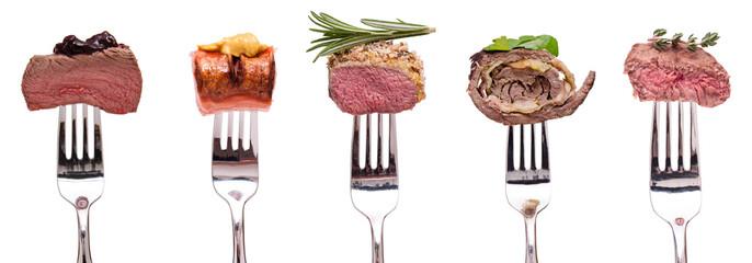 Fleisch vom Wild, Lamm, Rind und Roulade aund Wurst auf einer Gabel