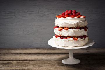 Pavlova, a Dessert with Layers of Meringue, Whipped Cream, and Berries on a Cake Stand