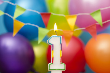 Happy Birthday number 1 celebration candle with colorful balloons and bunting