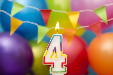 Happy Birthday number 4 celebration candle with colorful balloons and bunting