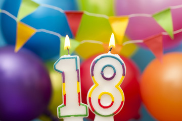 Happy Birthday number 18 celebration candle with colorful balloons and bunting