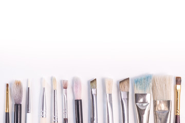 Set of paint brush on white background. Different models of brushes for painting isolated. A place for your inscriptions. Background for a site design or landing page about art and drawing. Flat lay