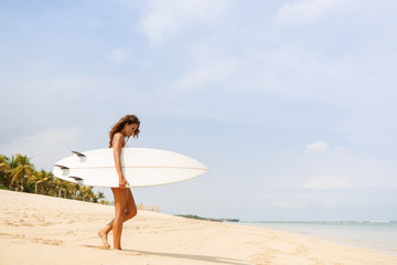 Beautiful fit surfing girl in sexy bikini swimwear with white surf shortboard surfboard blank board at sunrise or sunset on sand beach walk to ocean. Vacation concept. Summer holidays. Tourism, sport.