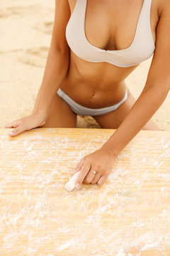 Close up view of a beautiful sporty surfing girl in sexy bikini wax her wooden surf shortboard surfboard board at sunrise or sunset on sand beach. Vacation concept. Summer holidays. Tourism, sport.