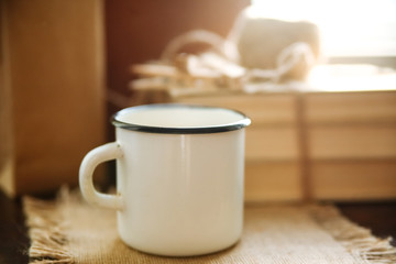 White iron mug on the windowsill