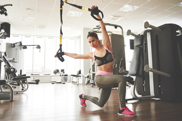Young fitness girl doing exercises on the machine at the gym