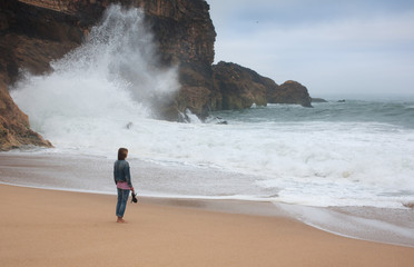 Young woman walking alone on the deserted coast of the Atlantic Ocean, Portugal