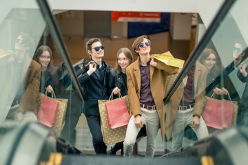 three girlfriends on escalator with shopping bags