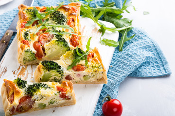 Delicious vegetarian homemade pie, sliced quiche with cherry tomatoes, broccoli and herbal cheese on old white cutting board. Healthy food concept.