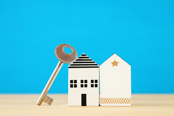 small house model with key over wooden floor. selective focus
