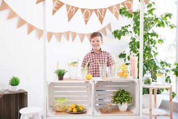 Cute little boy selling lemonade at counter
