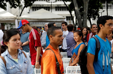 People stand in line to cast their votes during an unofficial plebiscite against Venezuela's President Nicolas Maduro's government and his plan to rewrite the constitution, in Caracas