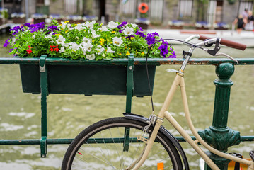 Bicycle parked on the bridge with flowers in Amsterdam Holland