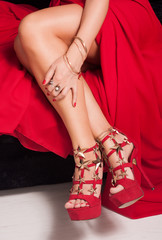 Close-up leg girl in a red dress sandals tying on a black background
