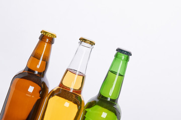 Refreshing alcoholic beverage, white background. Three bottles of beers with caps close up.