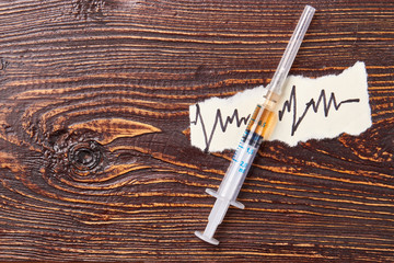 Syringe with liquid, paper note. Drugs effects on health and life.