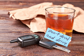 Driver keys, glass of alcohol, message. Full glass of alcohol, automobile keys, message, wooden background. Drunk drivers as a social problem.