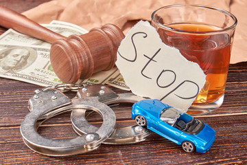 Still life drunk driving. Handcuffs, car, whiskey, american money, gavel on wooden background close up.