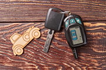 Cardboard car, key, wooden table. Vehicle remote device, textured background.
