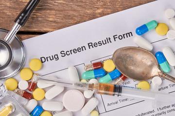 Drug screen result form, pills, stethoscope. Medicine, spoon, stethoscope, drug screen result form. Abuse of drugs harm for life.
