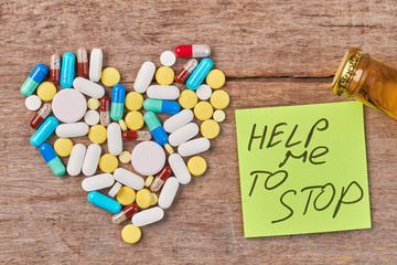 Help overcome alcohol addiction. Pills shaped heart, message, bottle, wooden background.