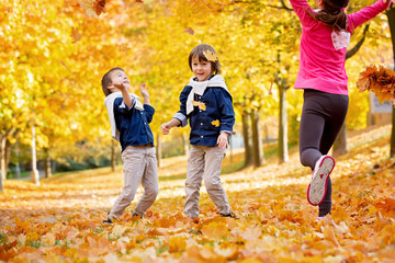 Happy children, boy brothers, playing in the park, throwing leaves, playing with fallen leaves in autumn
